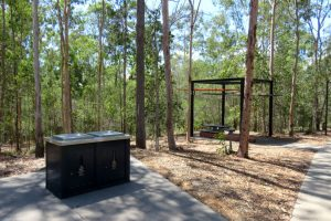 Electric bbqs and sheltered picnic table surrounded by trees