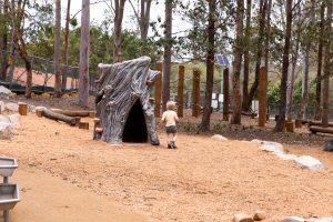 child running past tree trunk sculpture