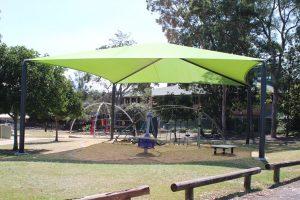 green shade sail over playground.