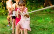 Group of happy children playing tug of war outside on grass. Kids pulling rope at park. Summer camp fun