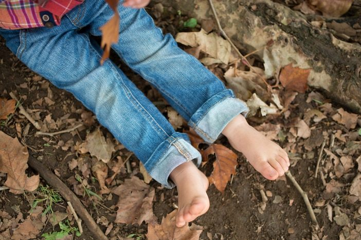 child feet in autumn leaves