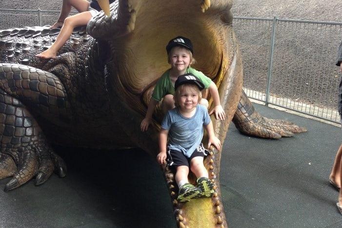 kids sitting in crocodile at australia zoo
