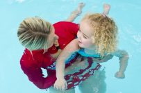 Girl in swimming pool with instructor