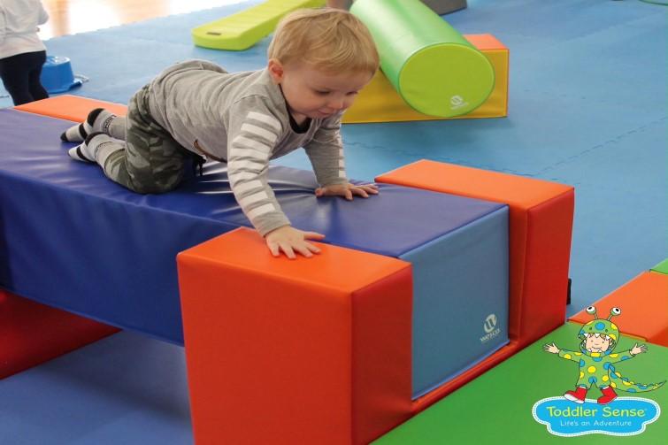 Toddler climbing over coloured blocks
