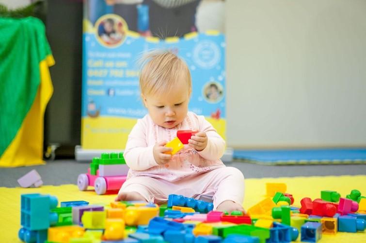 Toddler sitting playing with blocks