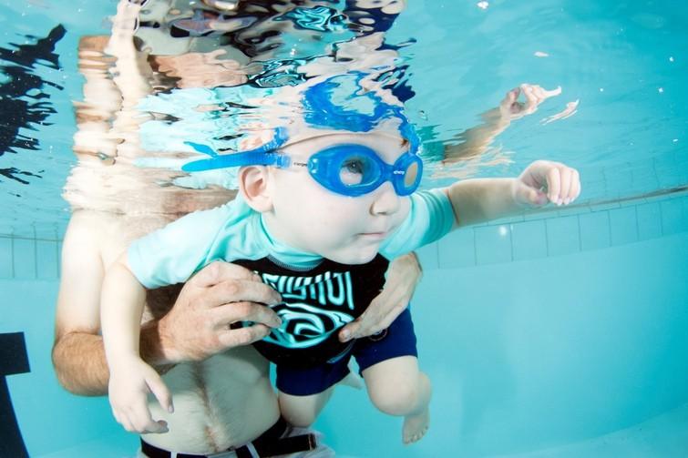 baby wearing goggles underwater