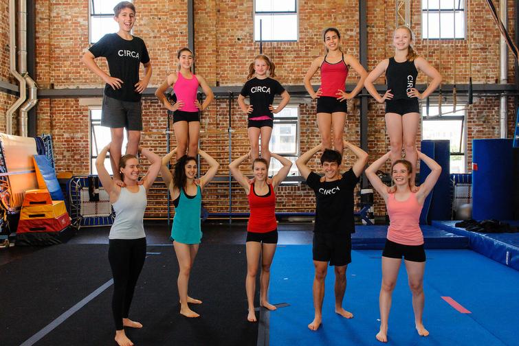 Circa circus troupe balancing on shoulders