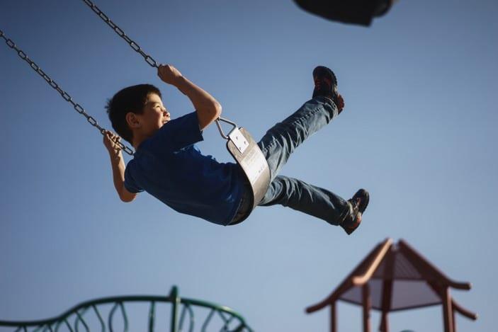 Swinging in the park under blue skies