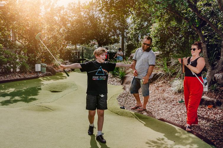 Family playing putt putt mini golf at Victoria Park