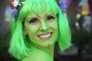 lady with green sparkly face paint and flowers in her green hair