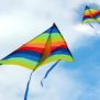 2 rainbow kites flying in the sky