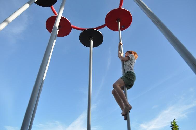 child climbing pole in playground