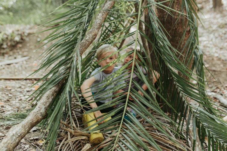 boy sitting under trees behind palm fronds