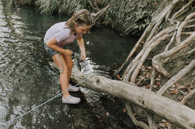 Girl standing in creek investigating