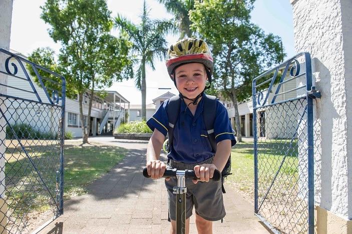 child riding to school with helmet
