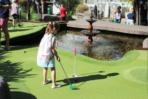 girl playing putt putt near pond