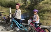 Two girls cycling near creek