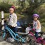 Two girls cycling near creek