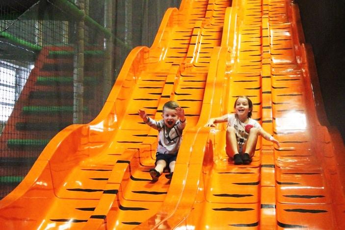 Kids playing on indoor slide at Urban Xtreme