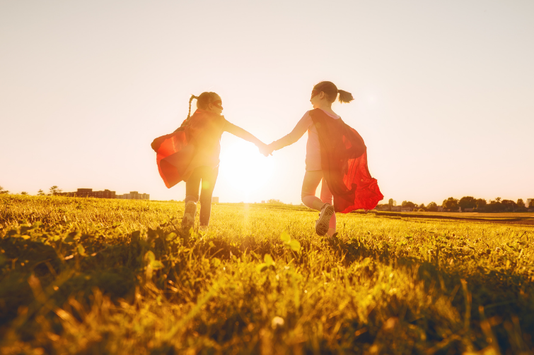 Children in superhero capes running through grass