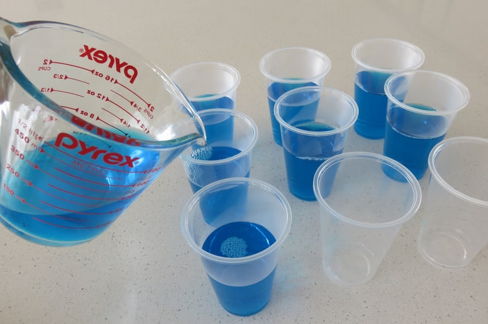 Jug pouring blue jelly into plastic cups