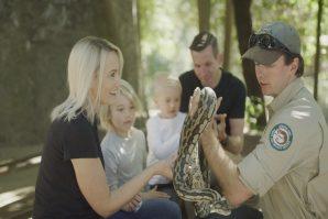 A family enjoying a snake encounter at David Fleay Wildlife Park