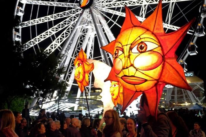 LUMINOUS Lantern Parade suns and wheel of Brisbane, crowds south bank
