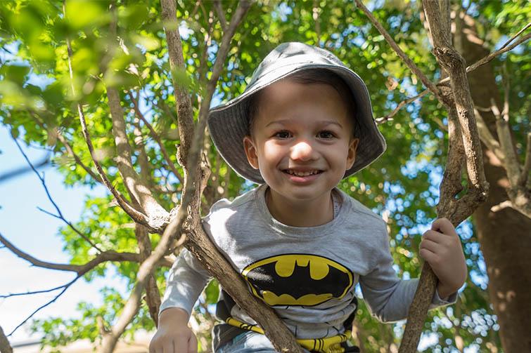 Boy in Batman tshirt smiling in tree