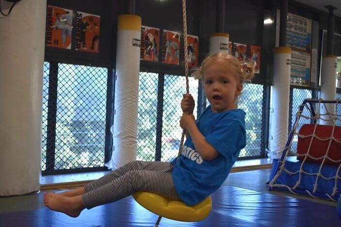 child on a swing in a Brisbane kindergym