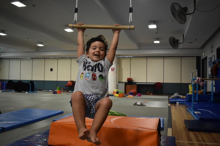 Happy boy on swing at kindergym class