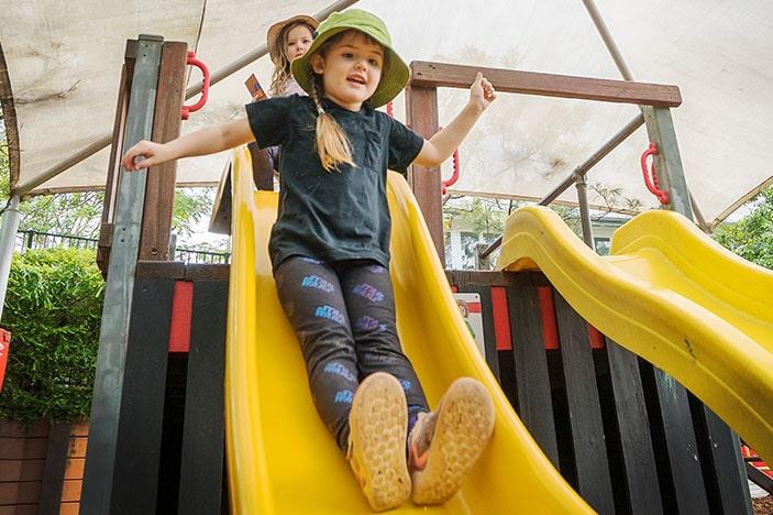 child with hat enjoying yellow slippery slide
