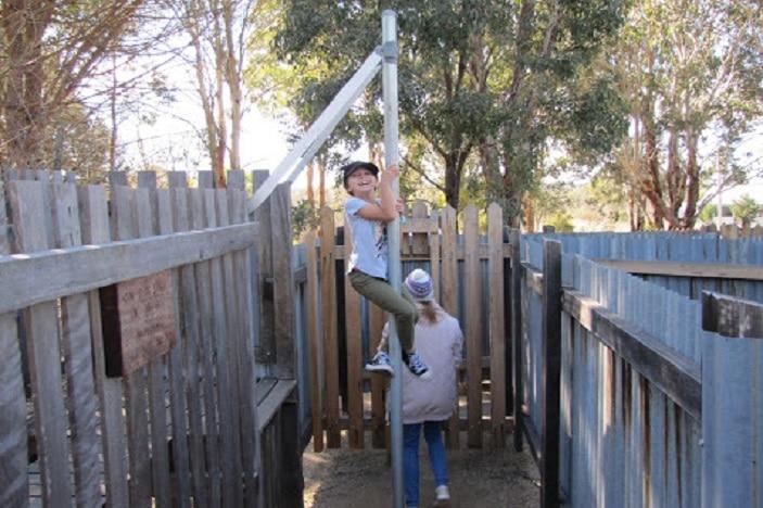 Girl climbing pole in Granite Belt Maze