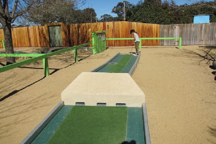 Girl playing mini golf at The Granite Belt Maze