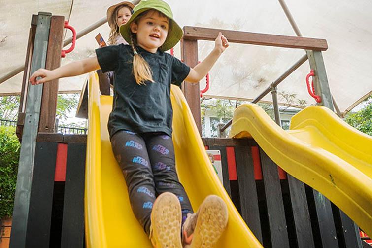 Girls in playground going down slide