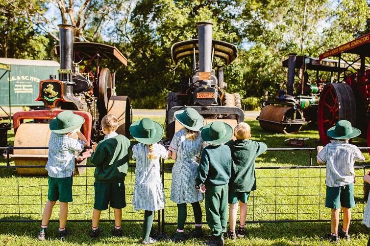children looking at an old steam engine.