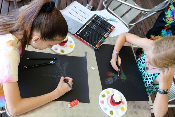 Art students sketching on black paper