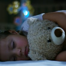 baby sleeping soundly with teddy bear