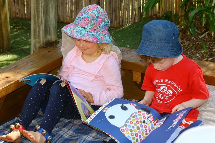 Kindergarten children looking at books and wearing hats