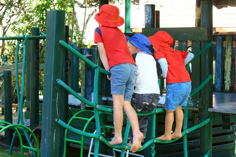 Children at kindergarten playing outside on climbing equipment