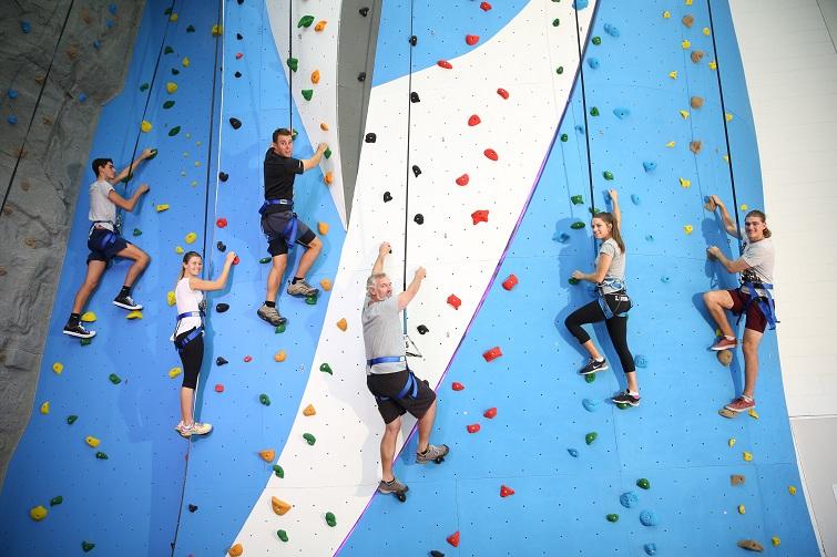 people climbing indoor rock climbing wall