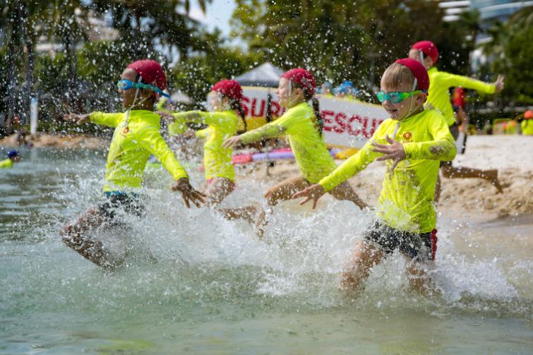 Little Lifesavers kids running into water on beach