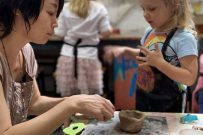 girl and teacher with clay at art class