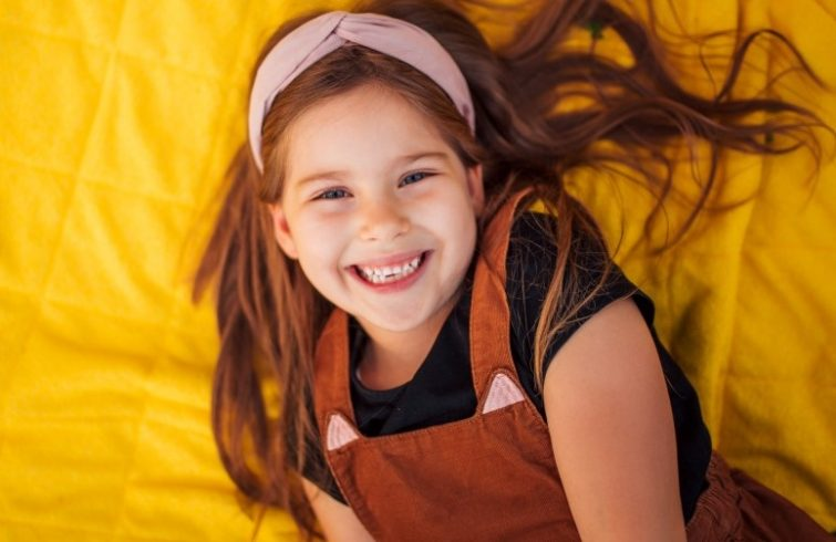 child with clean white teeth smiling at camera
