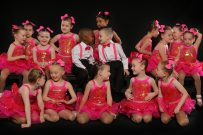 Group of children on stage during ballet performance in pink outfits