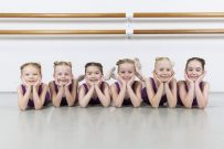 Smiling dancers lying in a row under barre