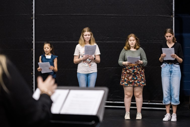 group of students on stage practicing for choir performance