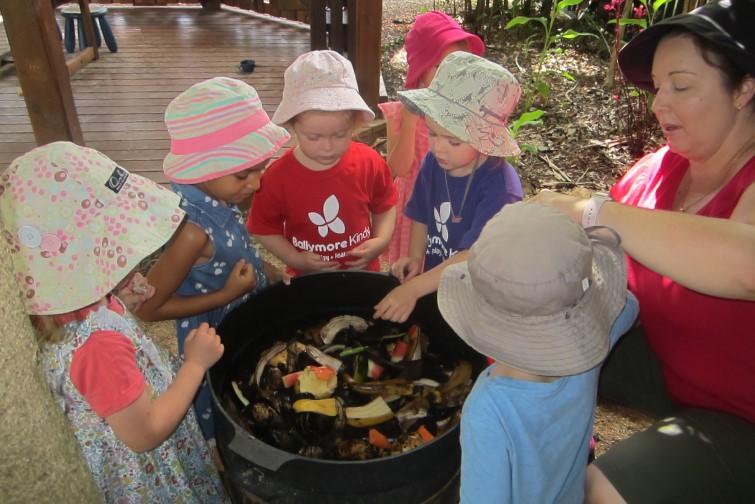children and kindy teacher composting