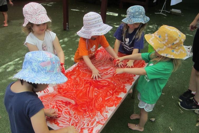 children finger-painting outside