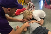 Child being instructed how to listen for breathing in first aid course