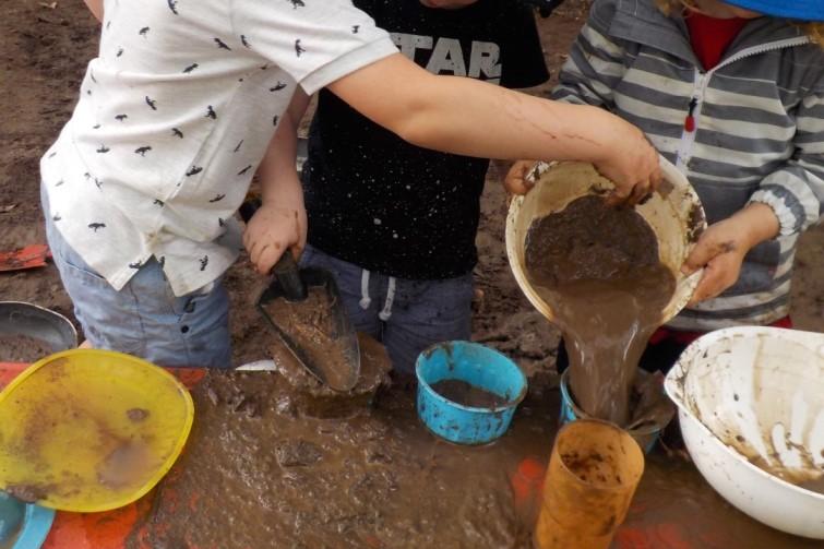 kindergarten kindergarten children playing with buckets and mud